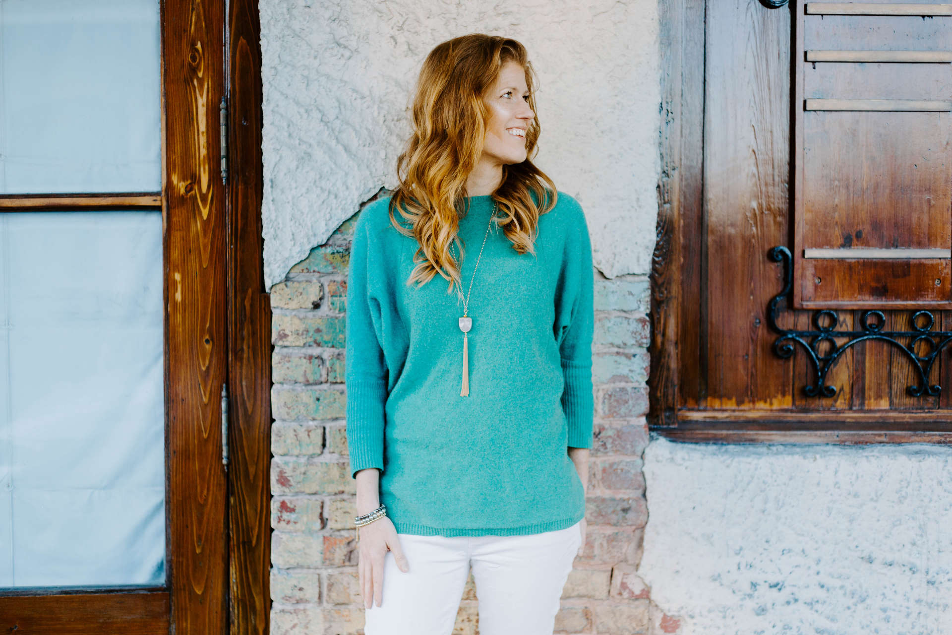 Mary Bielski in a teal shirt, up against a white wall